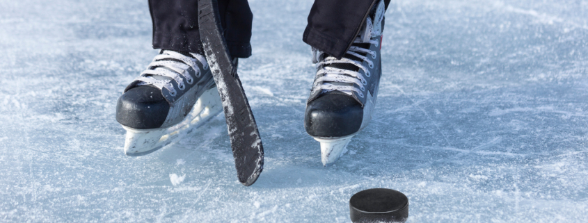 Black hockey skate on ice with sports equipment